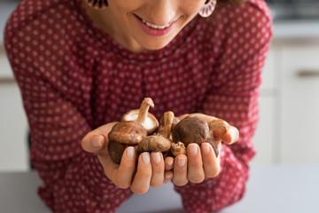 Closeup on young housewife holding shiitake mushrooms