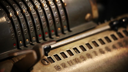 Close up of changing numbers on an old cashier with changing focus and shaky camera for dramatic impression