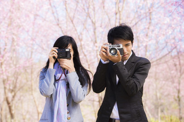 Man and girl photographed outdoors holding vintage camera.