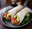 two vegan burritos with avocado, tomato and lentils - 77387977