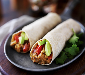 two vegan burritos with avocado, tomato and lentils