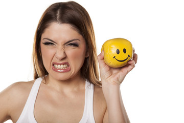 Mad woman holds in her hand a smiley ball