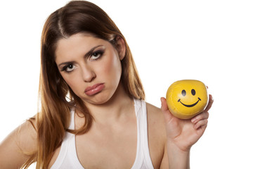 sad woman holds in her hand a smiley ball