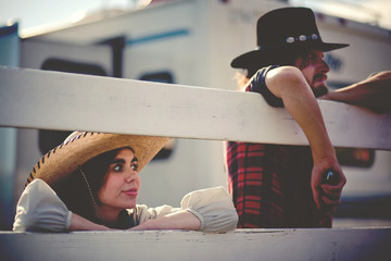 Couple wearing cowboy hats leaning on fence
