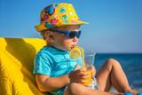 kid drinks juice against sea