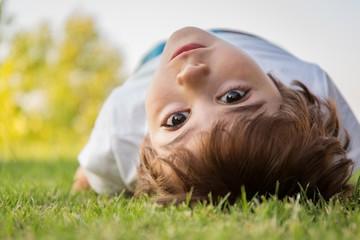 Boy (2-3) lying on lawn