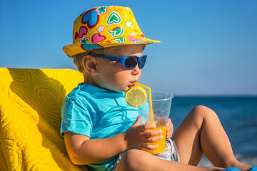 kid drinks juice against sea