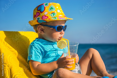 kid drinks juice against sea - 77390167