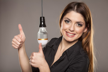 happy young woman showing thumbs up next to LED bulb