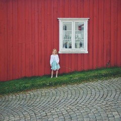 Norway, Girl (12-13) standing against red house