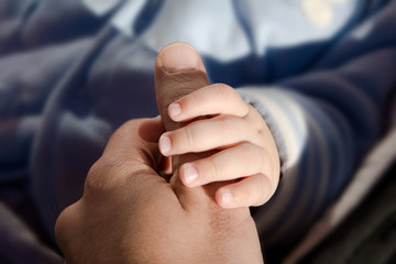 Baby holding man's hand