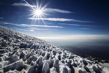 Sun and snow on mountainside