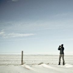 Usa, Wyoming, Woman watching wildlife through binoculars in snow-covered landscape