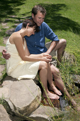 Couple sitting with feet in stream