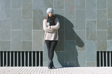 Portrait of young woman with winter clothes in front of stone wa