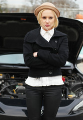 Upset woman standing in front of a broken down car