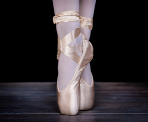 Close-up shot of feet of ballerina standing on tiptoes