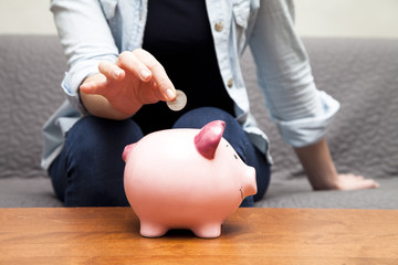 Woman dropping coin into piggy bank