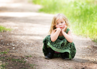 Girl (4-5) crouching on path