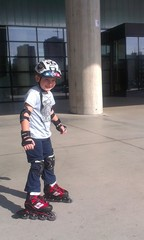 Young boy learning to ride on roller skates