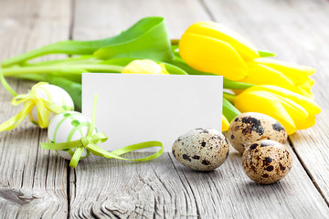Quail eggs and Easter eggs on wooden background