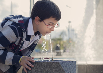 Spain, Cordoba, Boy (12-13) drinking water from fountain in park