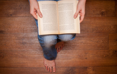 girl in jeans sitting and reading a book.