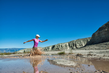 USA, Colorado, Woman cross-country running through muddy water