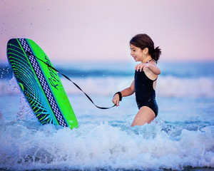 Girl (6-7) with surfboard playing in water