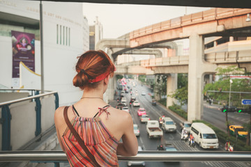 Young woman looking at traffic in Bangkok