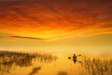 Man paddling in canoe across calm lake at sunset