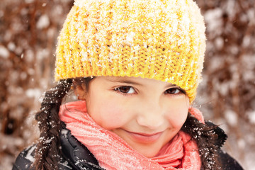 Pretty little girl (6-7) in braids and hat, smiling during snow fall