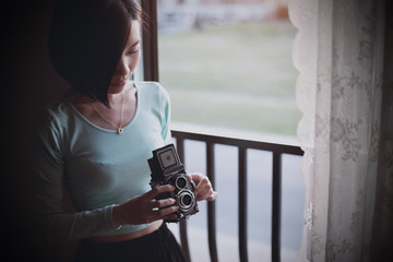 Canada, Quebec, Brossard, Young woman holding vintage camera