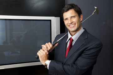 Businessman with golf club in the office
