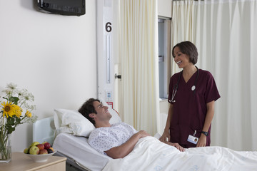 Hospital patient in bed talking with nurse