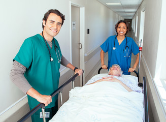 Two doctors pushing patient in bed along hospital corridor