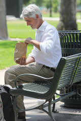 Businessman sitting on bench in park with his lunch
