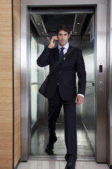 Businessman on phone stepping out of office elevator