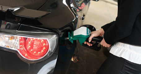 Woman dispensing fuel from a petrol pump