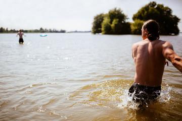 The Netherlands, Jsselmeer, Man throwing plastic flying disc across lake