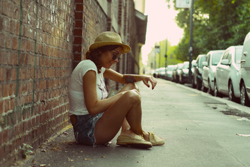 Italy, Lombardy, Milan, Woman sitting in street