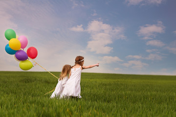 Two girls (2-3, 6-7) with balloons in field
