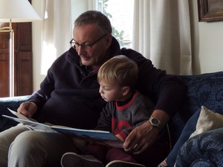 Grandfather and grandson reading book