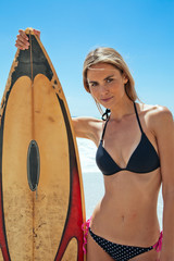 Young woman standing with surfboard on the beach