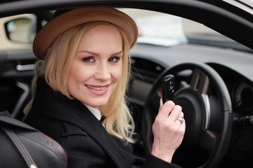 Pretty woman driver holding her car key in the car