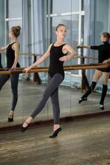 Young girls exercising during ballet class