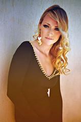 Elegant blonde woman wearing a black dress and dark eye make-up.
