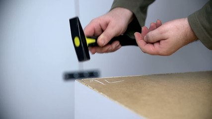 Nailing the nails into furniture with small hammer