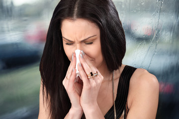 Woman with cold, flu season sneezes and tissue