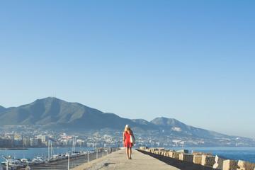 Woman in red walking down pier